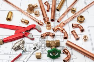 Plumbing Tools Arranged On House Plans whit wrench and pipe cutter