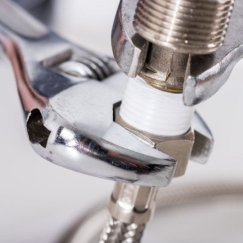 A Plumbing Contractor Tightens a Fixture Connection